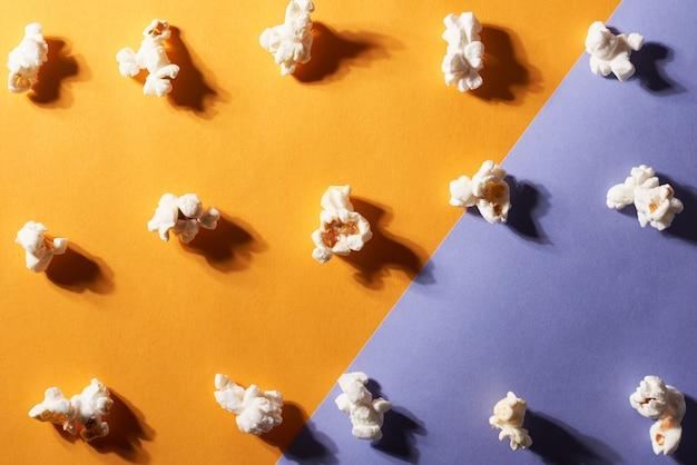 Gros plan de morceaux de pop-corn sur orange et violet. concept de nourriture.