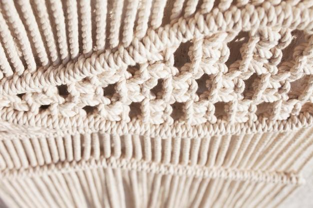 Gros plan sur un motif de texture macramé fabriqué à la main. concept de décoration naturelle de bricolage à tricoter moderne et respectueux de l'environnement à l'intérieur. macramé fait main 100% coton. passe-temps féminin.