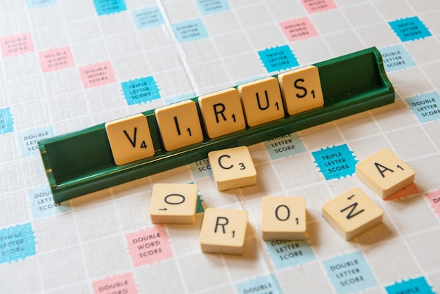Gros plan des mots corona et virus écrits sur un tableau de brouillage sous les lumières