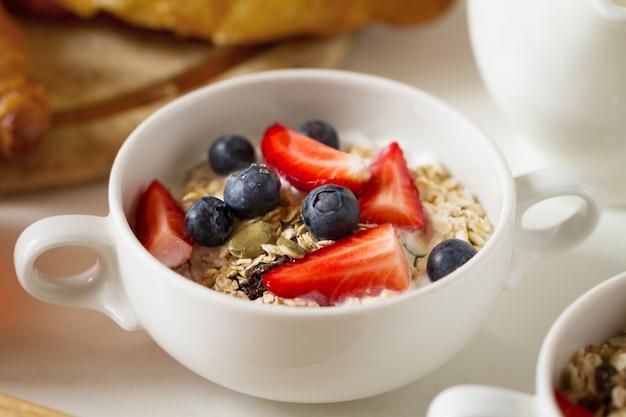 Gros plan de muesli appétissant savoureux avec de la farine d'avoine, des fruits, du yaourt dans un bol blanc. concept de restauration alimentaire sain du matin.