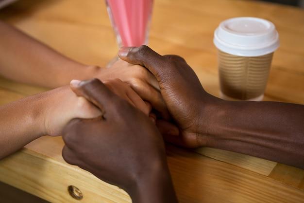Gros plan, de, multi ethnique, couple, tenant mains, dans, café-restaurant