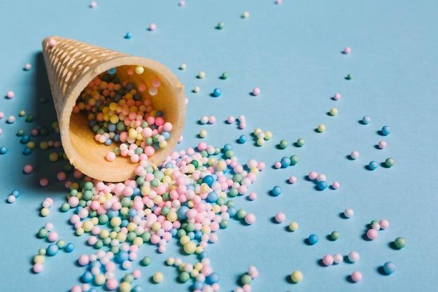 Gros plan, multicolores, paillettes, répandre, depuis, cône gaufre, sur, fond bleu