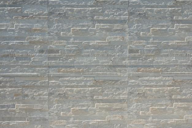 Gros plan d'un mur de briques grises, fond de texture de pierre moderne.