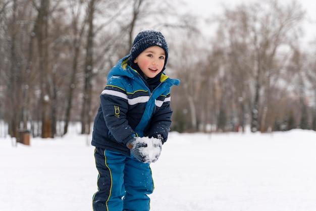 Gros plan n enfant heureux jouant dans la neige