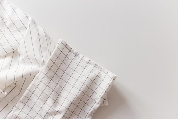 Gros plan de nappe à carreaux et rayé blanc, isolé sur blanc avec espace de copie.