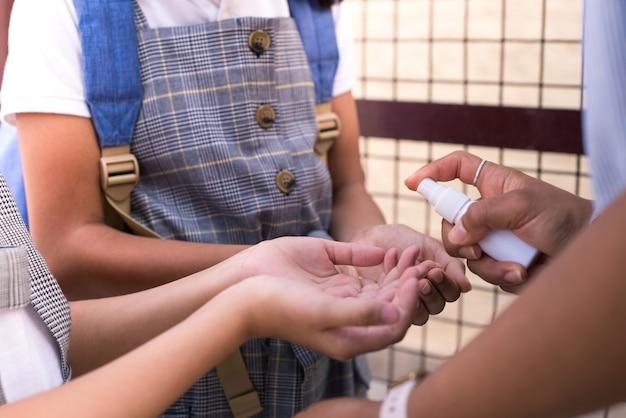 Gros plan de nettoyage des mains avec un désinfectant à l'école