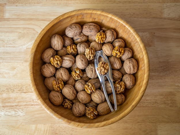 Gros plan de noix dans un bol brun sur fond de bois