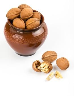 Gros plan de noix ouvertes en pot brun sur fond blanc