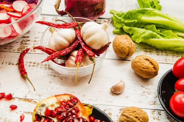 Gros plan de noix; piments rouges; grenade; salade; ail sur table