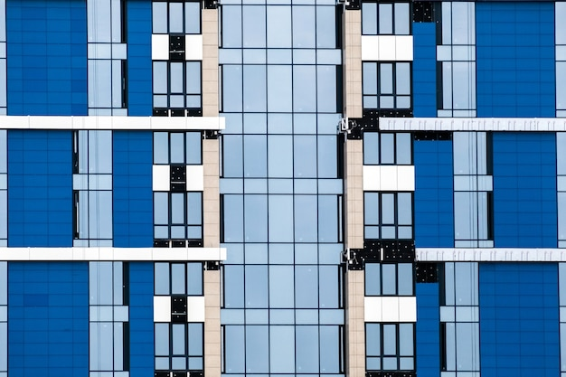 Gros plan sur de nombreuses fenêtres sur un extérieur bleu d'un immeuble d'appartements moderne. pour l'immobilier contexte.