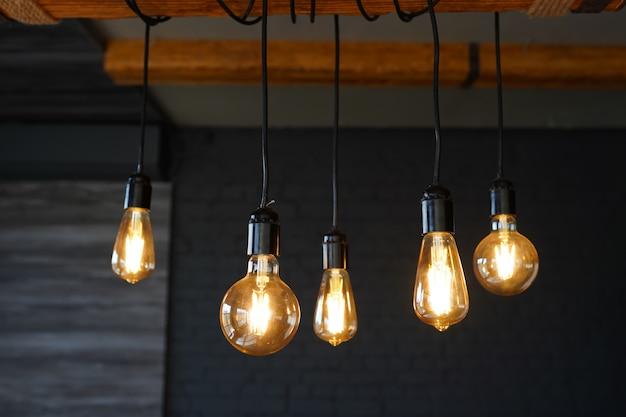 Gros plan de nombreuses lampes jaunes dans un café la nuit, pièce sombre