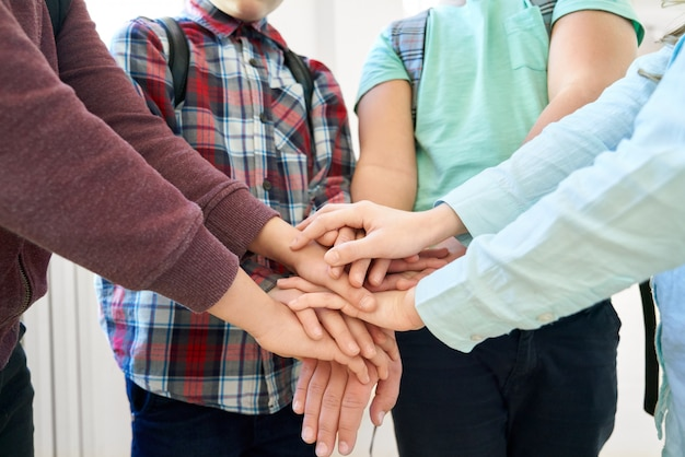 Gros plan de nombreuses mains d'enfants se touchant, se tenant sous l'autre.