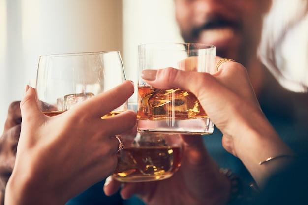 Gros plan de nombreuses personnes tinter des verres avec de l'alcool à un toast