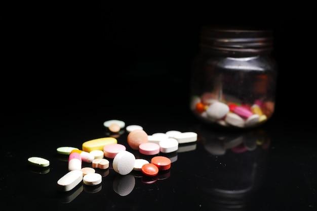 Gros plan de nombreuses pilules et capsules colorées sur fond noir