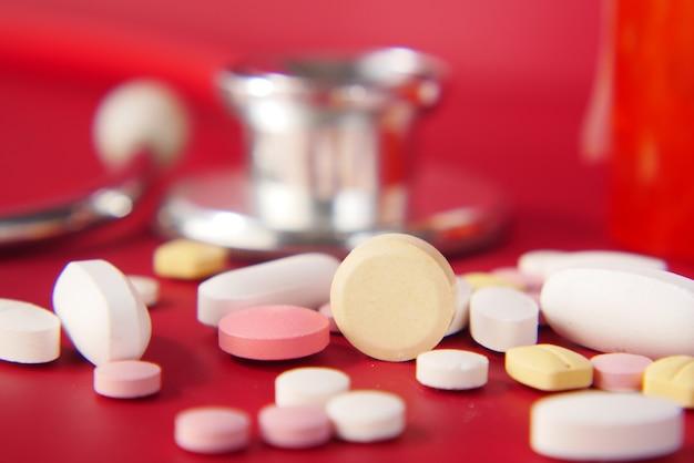 Gros plan de nombreuses pilules et capsules colorées sur fond rouge