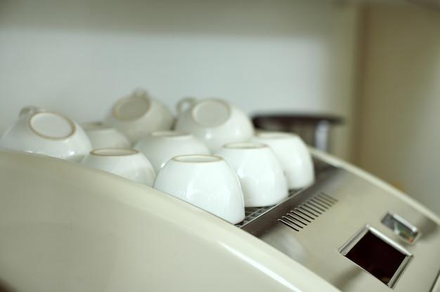 Gros plan de nombreuses tasses blanches propres vides inversées sur une machine à café.