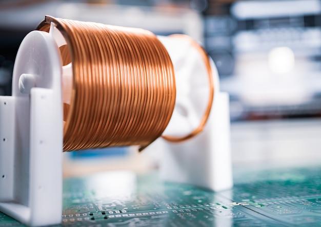 Gros plan de nombreux écheveaux de fil de cuivre torsadé reposent sur un microcircuit vert.
