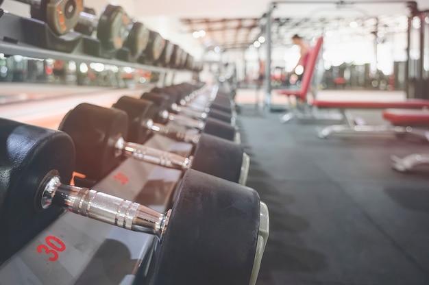 Gros plan de nombreux haltères en métal sur un support dans un centre de fitness sport
