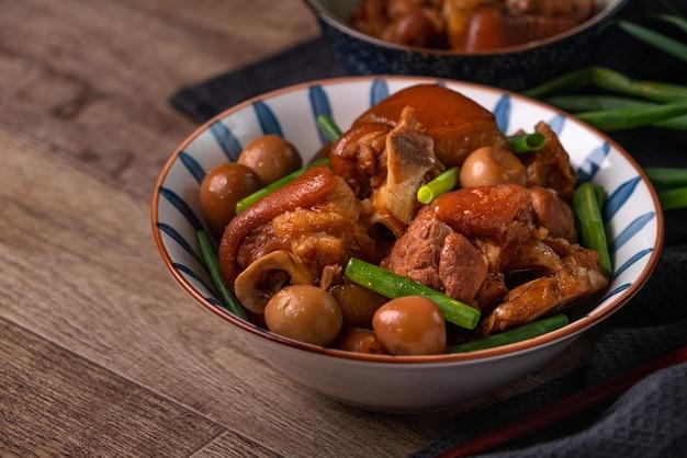 Gros plan de la nourriture traditionnelle taïwanaise jarret de porc dans un bol sur fond de table rustique.