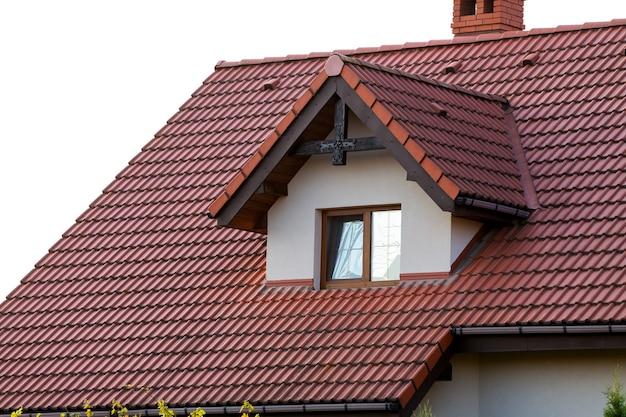 Gros plan sur un nouveau toit orange avec cheminée et petite fenêtre moderne. concept de toit moderne avec une petite fenêtre brune élégante.