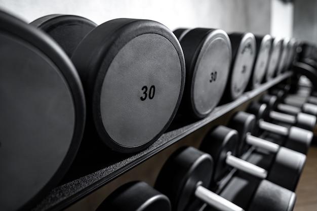 Gros plan de nouveaux haltères sur un rack dans une salle de sport