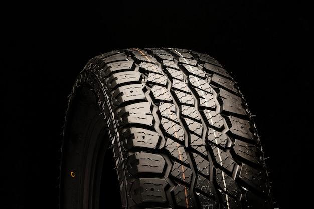 Gros plan de nouveaux pneus tout terrain sur un espace noir