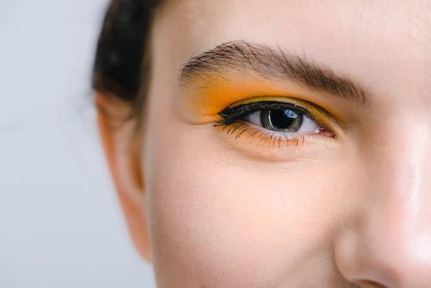 Gros plan de l'œil féminin. vue recadrée de la femme caucasienne avec un maquillage vif en regardant la caméra avec plaisir. concept d'apparence de personnes