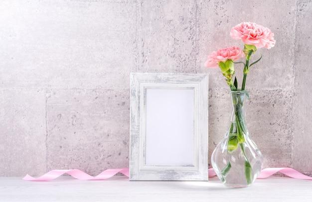 Gros plan de l'oeillet rose dans un vase avec cadre photo pour la fête des mères