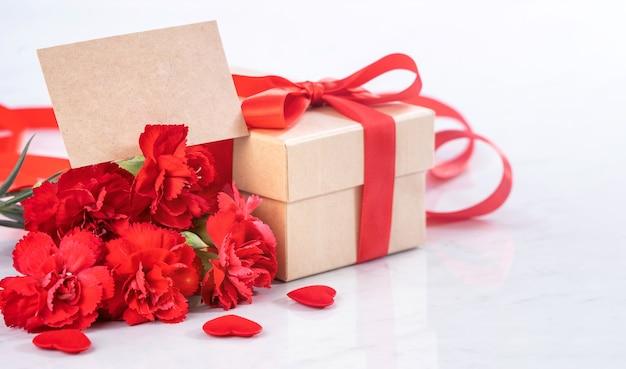 Gros plan de l'oeillet rouge avec boîte-cadeau pour la fête des mères