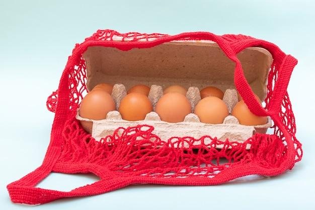 Gros plan d'oeufs crus naturels dans une boîte d'oeufs en carton et dans un sac de ficelle rouge. concept de nourriture saine.