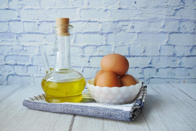Gros plan d'œufs dans un bol et d'huile de cuisson dans un bocal en verre