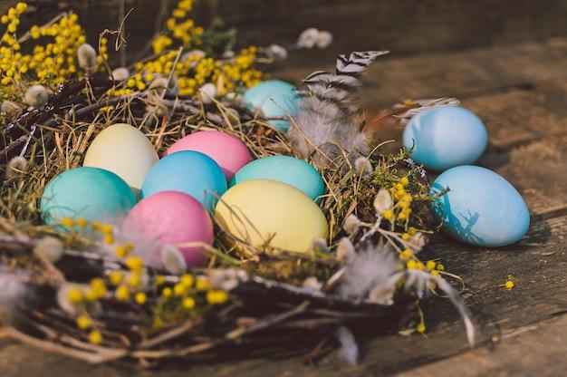 Gros plan, oeufs de pâques colorés dans un beau nid. dans le contexte d'une vieille planche de bois.