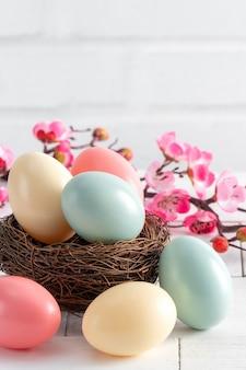 Gros plan d'oeufs de pâques colorés dans le nid avec fleur de prunier rose sur fond de table en bois blanc brillant.
