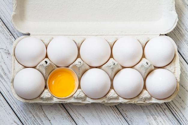 Gros plan des œufs de poule bio blanc frais dans le bac à papier et le jaune d'oeuf sur fond de bois clair. vue de dessus