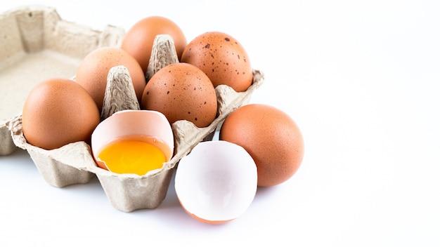 Gros plan des œufs de poule crus dans une boîte à œufs et une coquille isolée