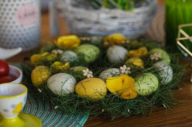 Gros plan d'oeufs tachetés verts, jaunes et blancs peints décorés d'une couronne verte avec des fleurs décoratives en bois sur la table.