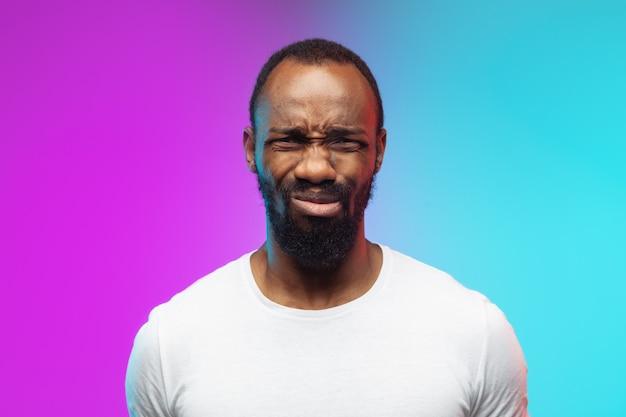 Gros plan offensé. portrait de jeune homme afro-américain sur fond dégradé en néon. beau modèle masculin dans un style décontracté, chemise blanche. concept d'émotions humaines, d'expression faciale, de ventes, d'annonces.