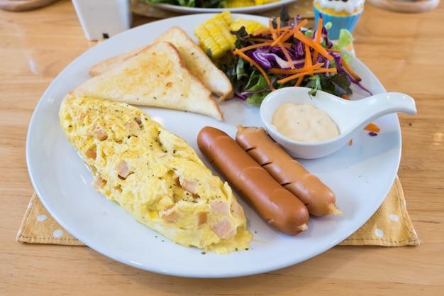 Gros plan d'une omelette avec du jus d'orange, des croissants, des céréales et des fruits sur une table en bois. régime équilibré.