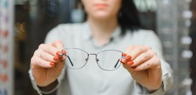 Gros plan de l'optométriste, opticien donnant des lunettes pour essayer