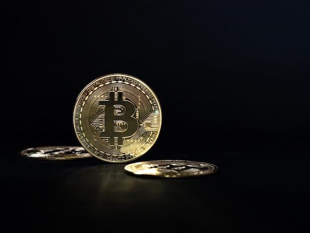 Gros plan d'or bitcoin sur fond noir avec mise au point sélective