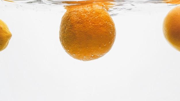Gros plan d'oranges juteuses fraîches tombant dans l'eau