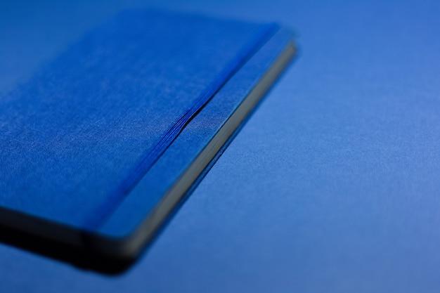 Gros plan d'un ordinateur portable bleu sur un mur bleu.