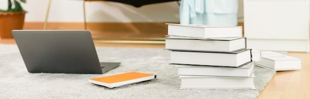 Gros plan sur un ordinateur portable et des livres sur le tapis à la maison