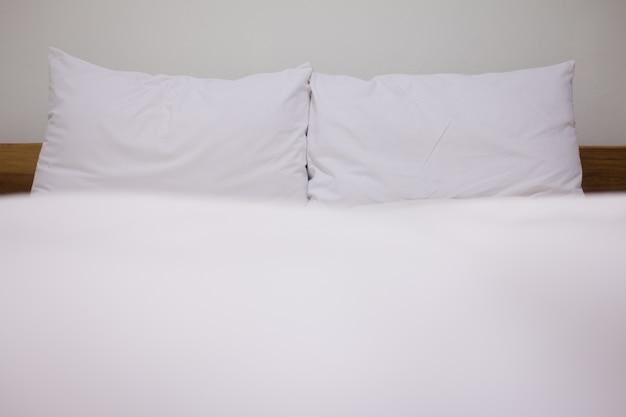 Gros plan de l'oreiller blanc et des draps sur le fond de la chambre des murs blancs naturels, le concept du lit désordonné