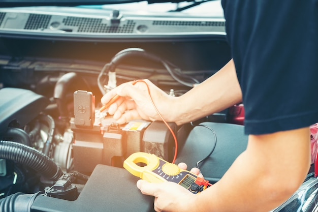 Gros plan outil et main de mécanicien en réparation de voiture au cours de la recherche de la cause du problème