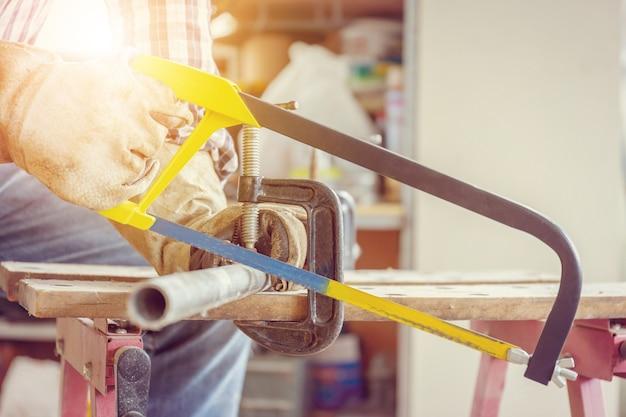 Gros plan d'ouvrier artisan scier un tuyau d'acier