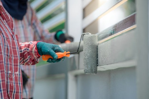 Gros plan d'un ouvrier peignant les murs de la maison à la main et au pinceau. peinture grise ou couleur ciment
