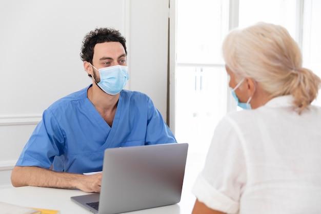 Gros plan sur pacient parlant au médecin au sujet du vaccin