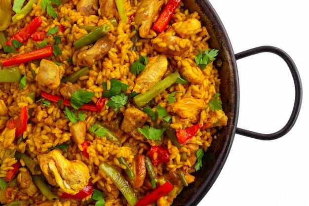 Gros plan de la paella espagnole arroz con pollo avec du poulet sur fond blanc