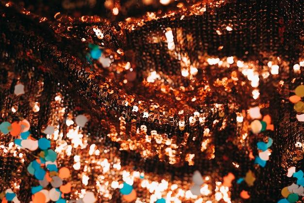 Gros plan de paillettes brillantes avec des confettis colorés
